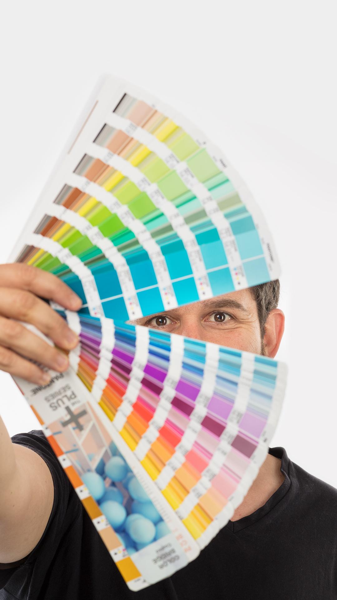 Wellness Brand Design Bernardo Covas Logo & Identity Designer holding a Pantone guide